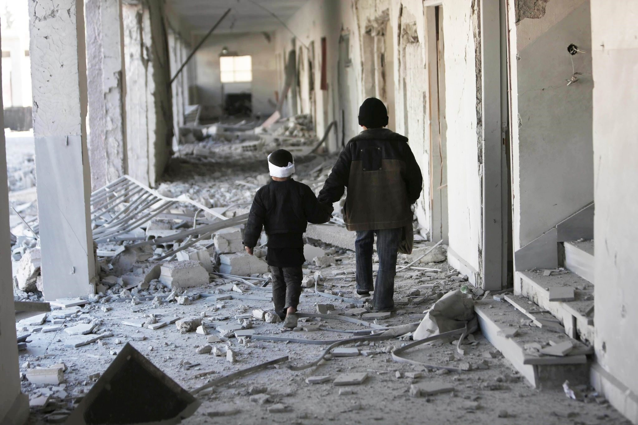 In this Nov. 25, 2015 photo provided by Save the Children, two children walk through the corridors of a destroyed school in Eastern Ghouta, Syria. (Photo by Save the Children via AP)