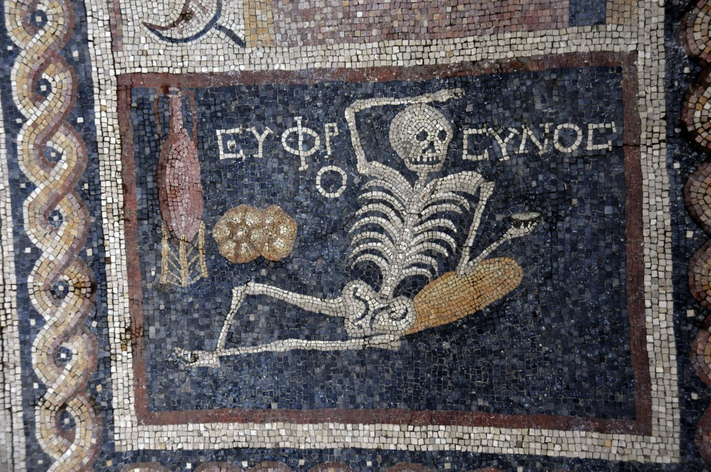 A 2,400 year old Roman mosaic depicts a skeleton lying down with a jorum in his hand, a wine pitcher and bread on the side with an inscription translated as u201cbe cheerful, enjoy your life.u201d