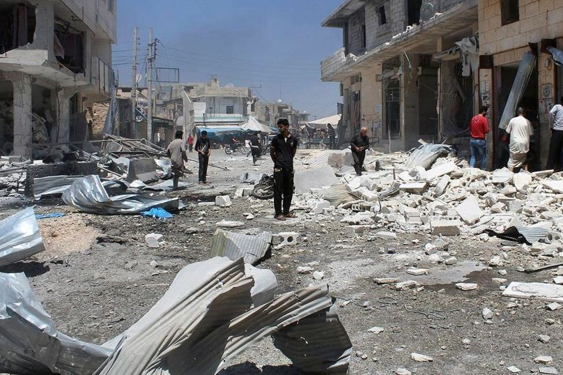 Aleppo residents inspect damaged shops after airstrikes hit a market.