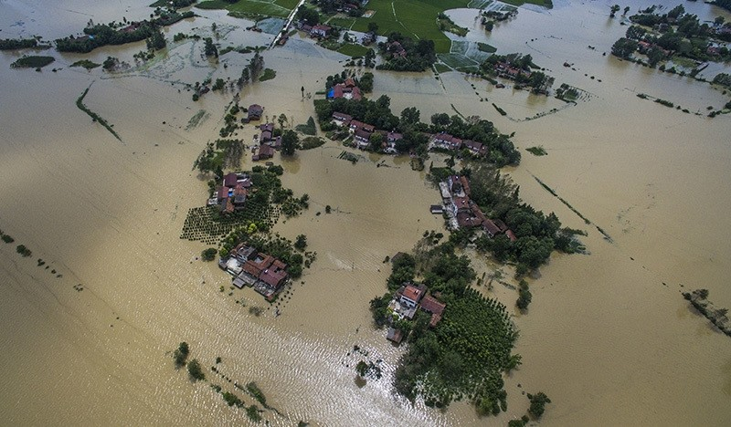 This Wednesday photo released by Xinhua News Agency, shows village houses and field partially submerged by flood waters in Gaoyang Town, Shayang County, central China's Hubei Province. (Xinhua via AP Photo)
