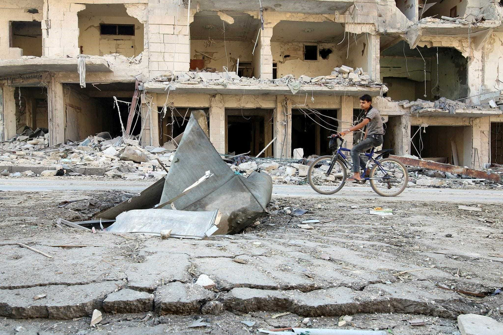 A man rides a bicycle near damaged ground in the opposition-held besieged al-Sukkari neighborhood of Aleppo, Syria, Oct. 19.