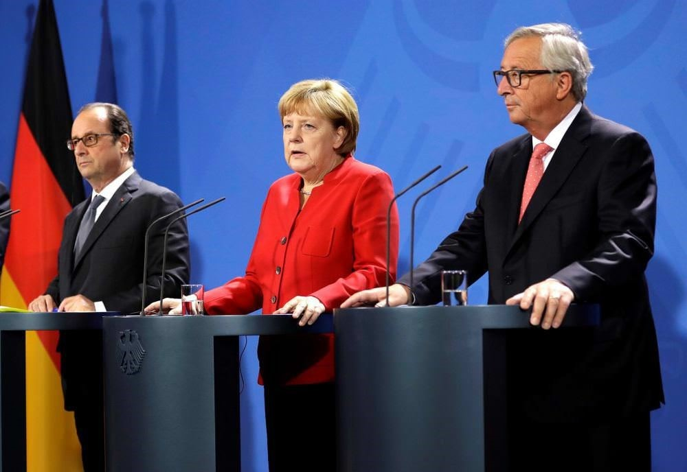 French President Francois Hollande, German Chancellor Angela Merkel and European Commission President Jean-Claude Juncker with representatives of the European Round Table of Industrialists in the chancellery in Berlin, Germany, Sept. 28.