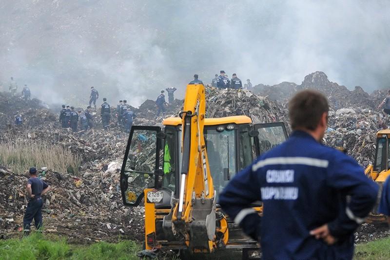 Rescue workers investigate a trash dump near Grybovychi village near Lviv, Ukraine, May 30, 2016.