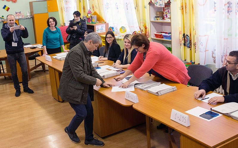 Romania's prime Minister Dacian Ciolos receives his ballots,for the parliamentary elections, before voting, at a polling station in Zalau city (EPA Photo)