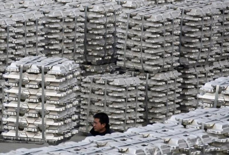 A worker walks among piles of aluminium ingots at a storage of aluminium plant in Yuncheng, Shanxi province January 7, 2010. (Reuters Photo)