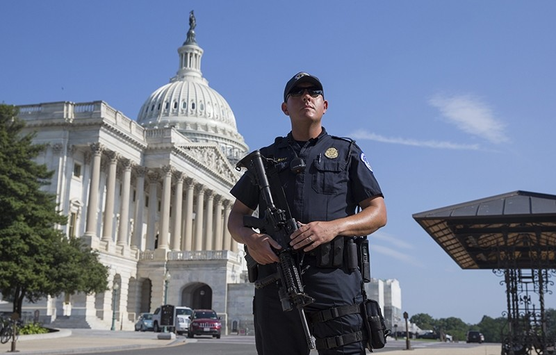 A US Capitol Police officer holds a firearm outside the US Capitol Building while it is on lockdown, in Washington, DC, USA, 08 July 2016 (EPA Photo)