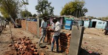 India hastily builds wall along slum ahead of Trump visit