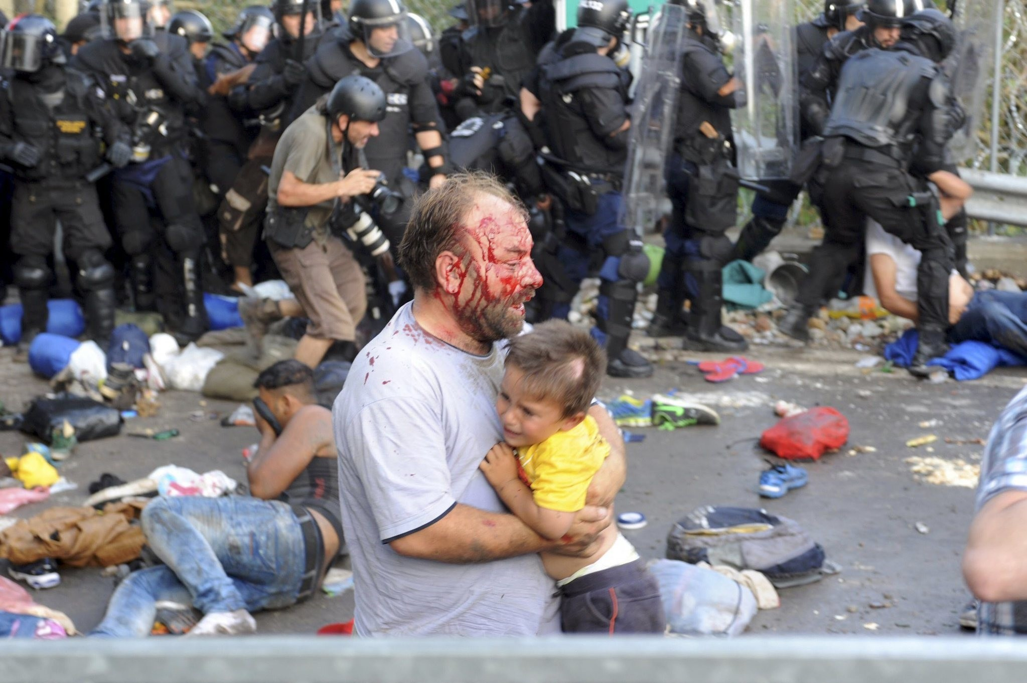 An injured migrant carries a child during clashes with Hungarian riot police at the border crossing with Serbia in Roszke, Hungary September 16, 2015. (Reuters Photo)