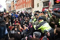 Demonstrators sit down at 10th Street near Pennsylvania Avenue to prevent spectators from reaching one of the entrances to the parade route to protest Trump. (EPA Photo)