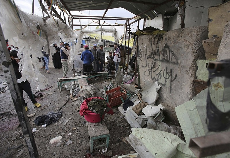 Citizens inspect the scene after a car bomb explosion at a crowded outdoor market in the Iraqi capital's eastern district of Sadr City, Iraq, Monday, Jan 2, 2017 (AP Photo)