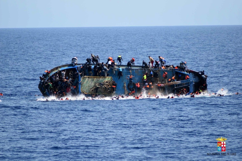 People jump out of a boat right before it overturns off the Libyan coast, May 25.