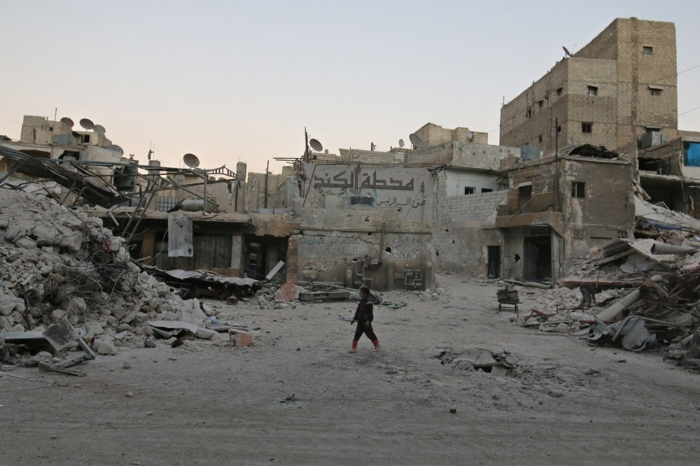 A boy walking amid damaged buildings in the moderate-held area of al-Kalaseh neighborhood in Aleppo, Syria, Sept. 29, 2016.