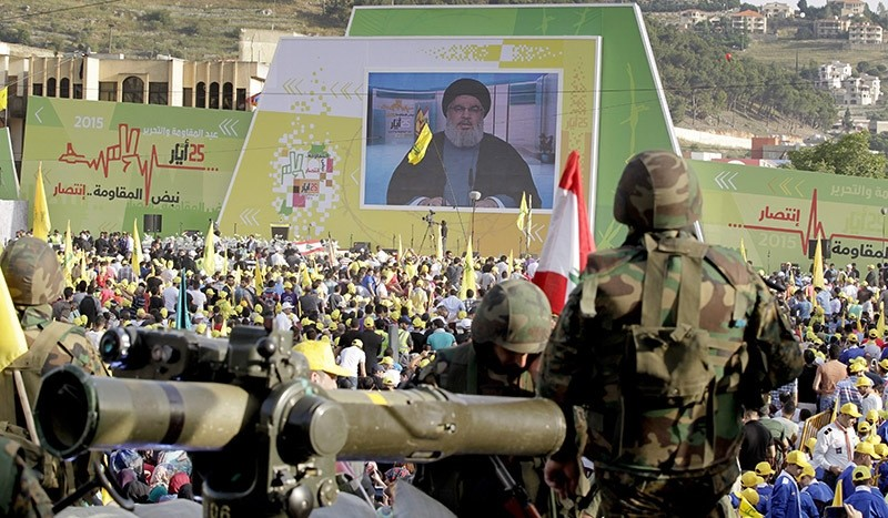 Hezbollah supporters listening to a speech by leader Hassan Nasrallah (on screen), as he delivers a speech on May 25, 2015 to celebrate the 15th anniversary of the Israeli withdrawal from south Lebanon. (EPA Photo)