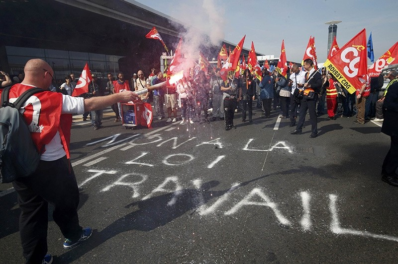 Striking employees hold French CGT labour union flags during a demonstration against the labour reforms law at the Charles de Gaulle Intu2019l Airport in Roissy, near Paris, France, June 7, 2016. The slogan reads ,No to the labour law,. (Reuters Photo)