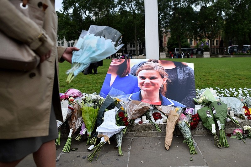 Floral tributes sit by a picture of slain Labour MP Jo Cox in Parliament Square, central London on June 17, 2016 (AFP Photo)
