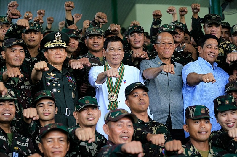 Philippines President Rodrigo Duterte (C) clenches fist with members of the Philippine Army during his visit at the army headquarters in Taguig city, metro Manila, Philippines October 4, 2016. (Reuters Photo)