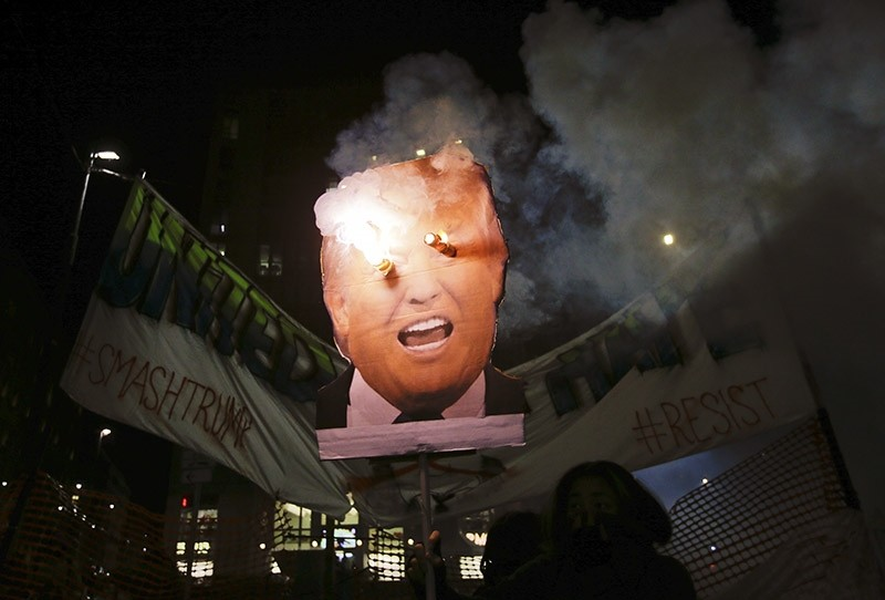 Protesters burn a picture of U.S. President Donal Trump. Jan. 20, 2017. (AP File Photo)