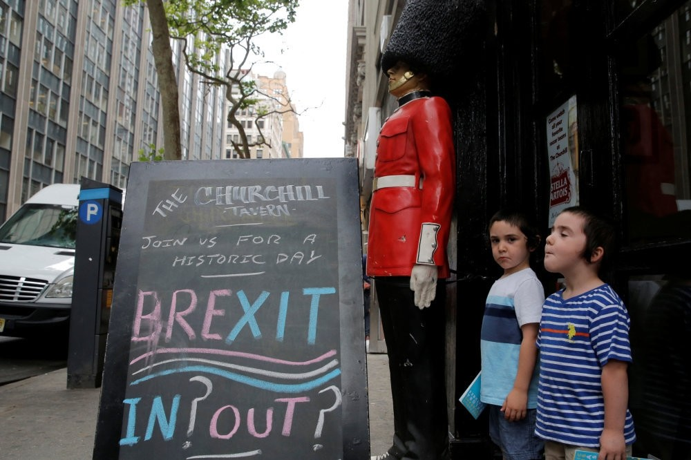 Children standing next to a chalkboard in Manhattan, U.S. on June 24, 2016, advertising the Brexit on the day the British went to a referendum to vote on whether the U.K. should remain in the EU or leave.
