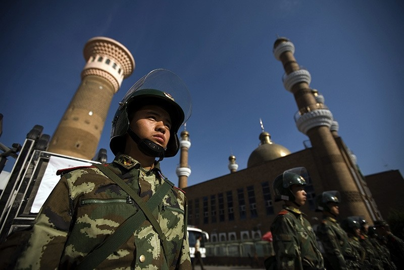 Security forces patrol the entrance to a mosque hours before Friday prayer in Urumqi, Xinjiang province, China, 10 July 2009. (EPA Photo)