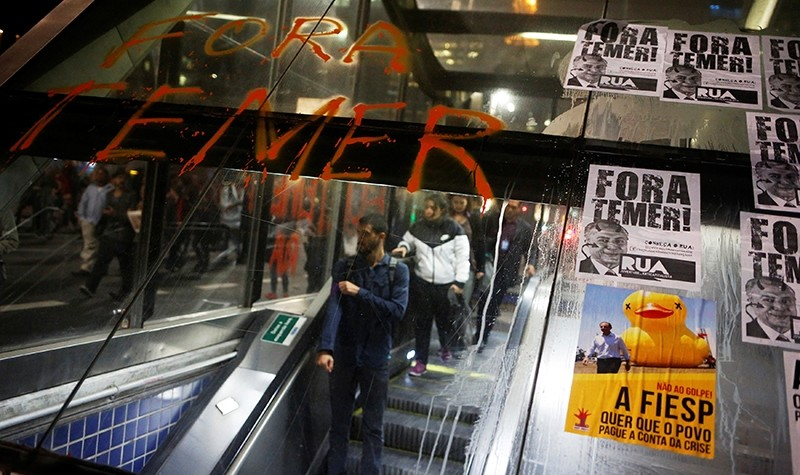 People go down the escalator in front of a phrase and posters with the image Brazil's interim President Michel Temer at the entrance of a subway (Reuters Photo)