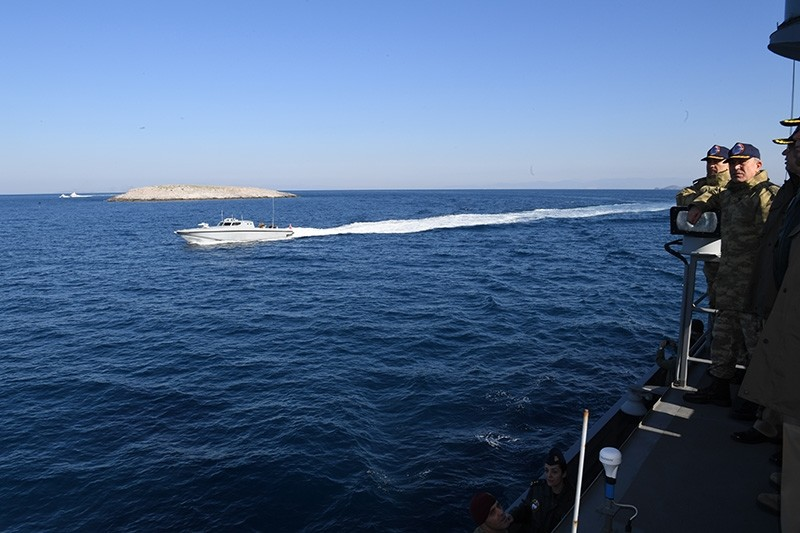 Turkish Chief of Staff Gen. Hulusi Akar carries out an inspection on TCG Meltem torpedo boat, while a small Greek patrol boat passing next to the vessel. One of the Kardak islets is seen in the background. (Photo: Turkish Armed Forces)