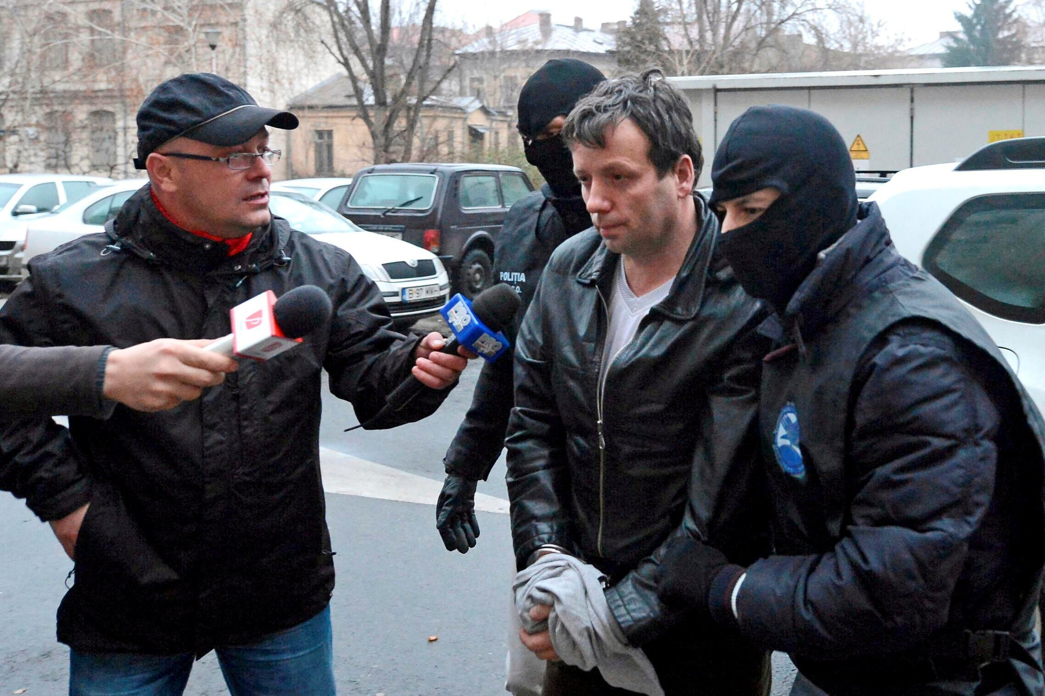 Marcel Lazar Lehel is escorted by masked policemen in Bucharest, after being arrested in Arad, 550 km (337 miles) west of Bucharest January 22, 2014. .(REUTERS Photo)