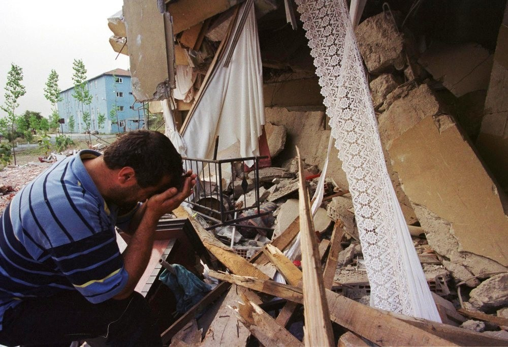 An earthquake survivor weeps next to his destroyed house in the western town of Seymen, u0130zmit in 1999.