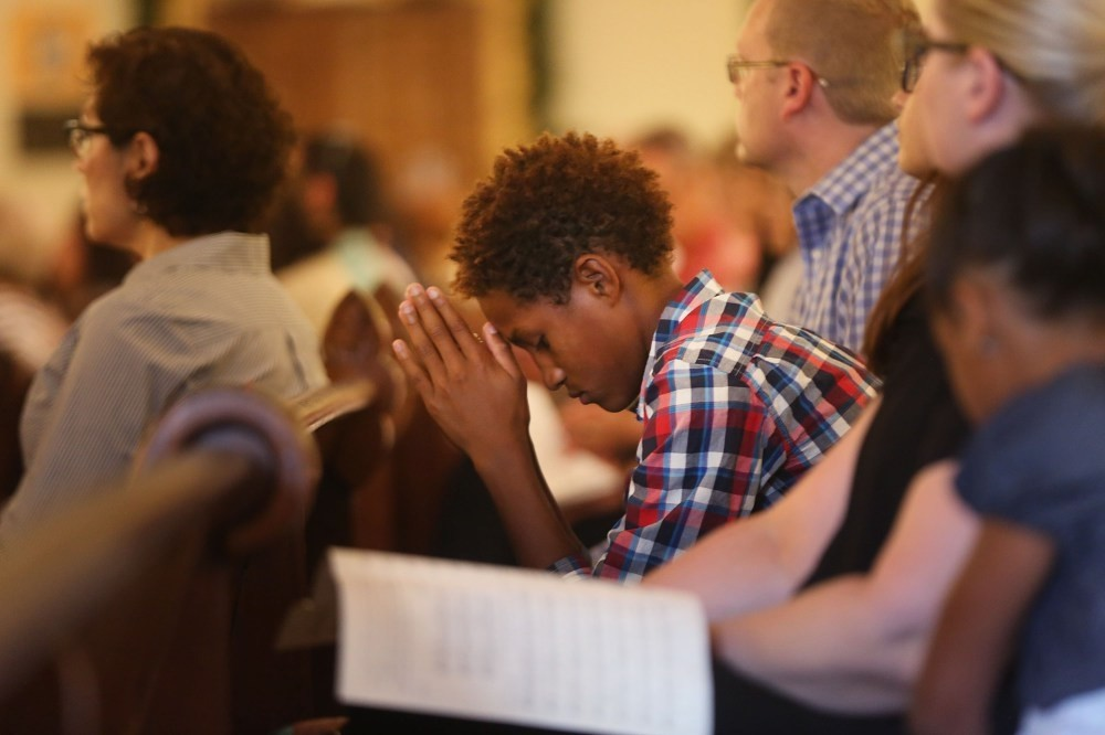 A teenager prays at a Mass for Hope and Healing held at Cathedral Shrine of the Virgin of Guadalupe in Dallas, Texas.
