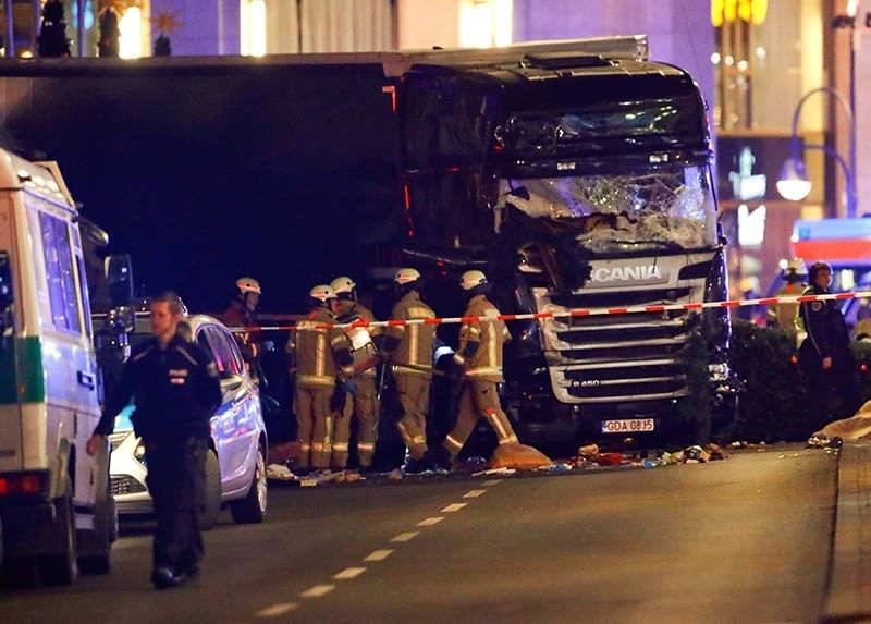 Police and emergency workers stand next to the crashed truck at the site of the suspected terror attack in Berlin, Germany on Dec. 19, 2016. (Reuters Photo)