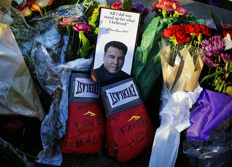 Boxing gloves and a message sit among flowers at a makeshift memorial to Muhammad Ali at the Muhammad Ali Center, Saturday, June 4, 2016, in Louisville, Ky. Muhammad Ali died Friday at age 74. (AP Photo)
