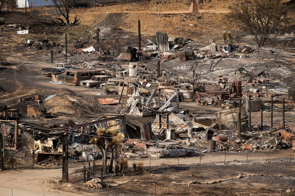 Scorched cars and trailers burned by the Blue Cut fire line a residential street in California.