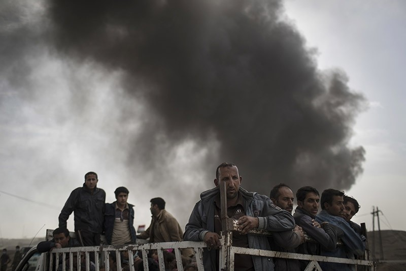 Displaced people stand on the back of a truck at a checkpoint near Qayara, south of Mosul. (Photo AP)
