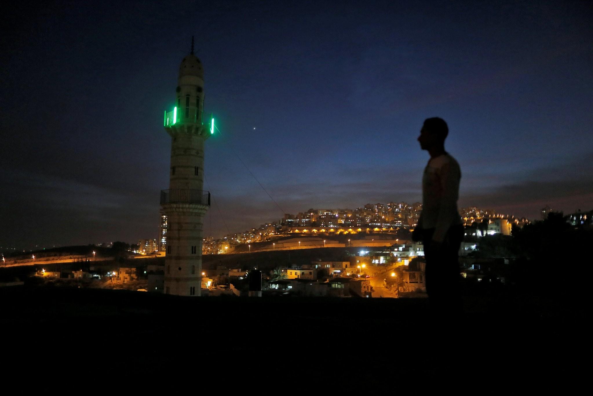 A man stands near a mosque opposite to a neighborhood in east Jerusalem November 13, 2016. (REUTERS Photo)