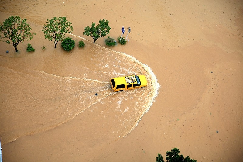 An automobile is seen passing a flooded street in Rongjiang, Guizhou Province, China, July 2, 2016. (Reuters Photo)