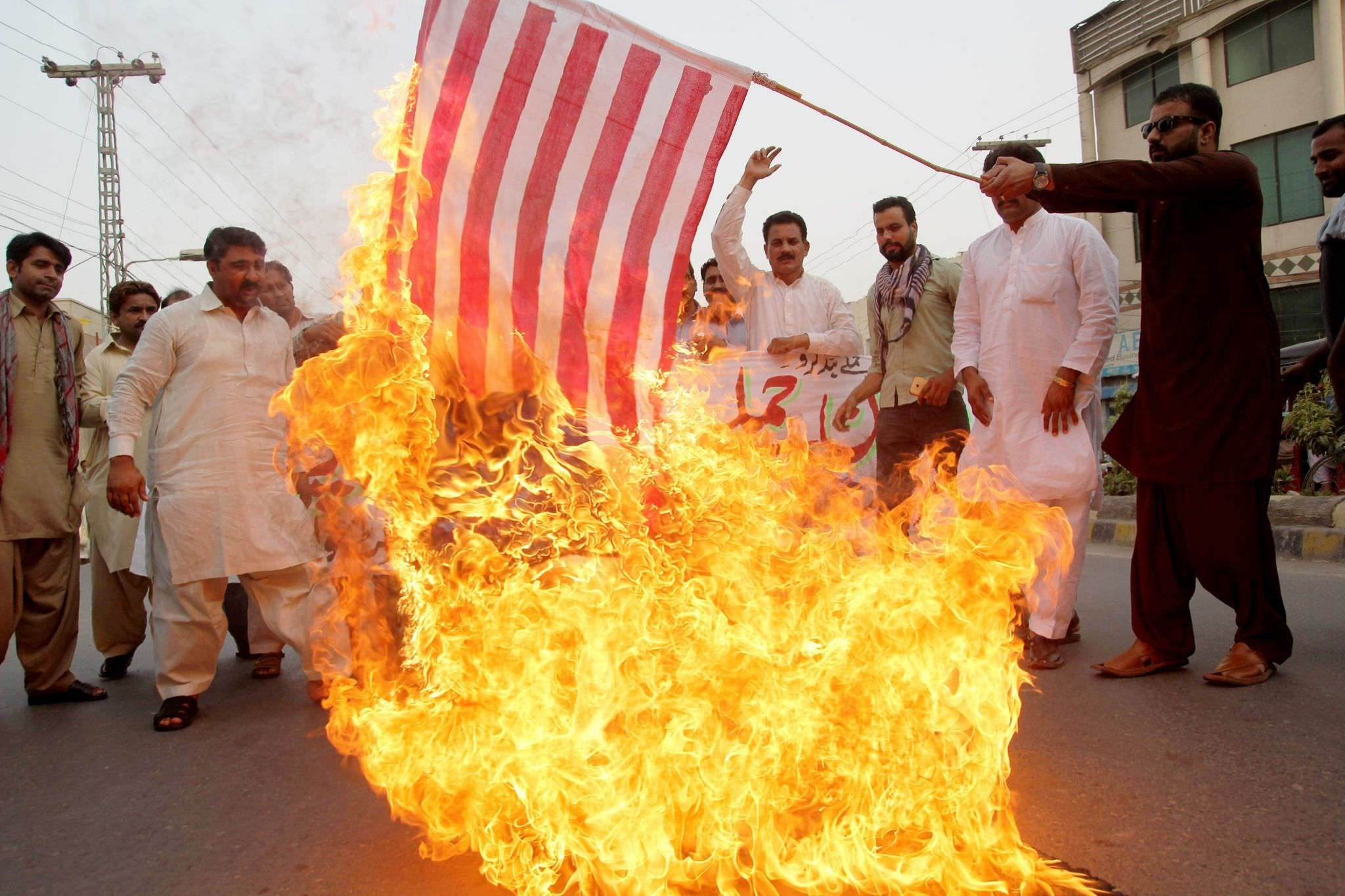 A Pakistani demonstrator holds a burning US flag as others shout slogans during a protest in Multan on May 24, 2016, against a US drone strike in Pakistan (AFP Photo)