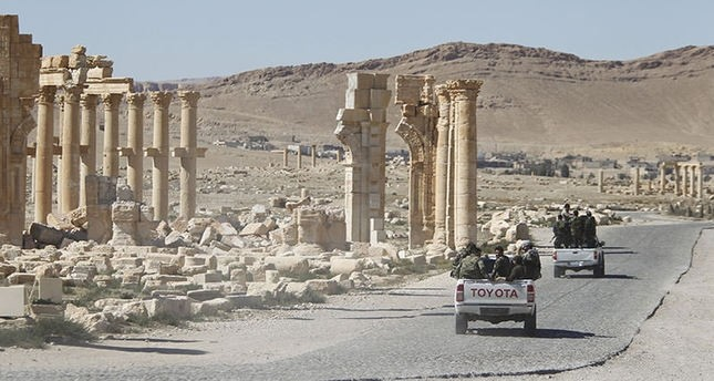 Syrian army soldiers drive past the Arch of Triumph in the historic city of Palmyra, in Homs Governorate of Syria, April 1, 2016 (Reuters Photo)