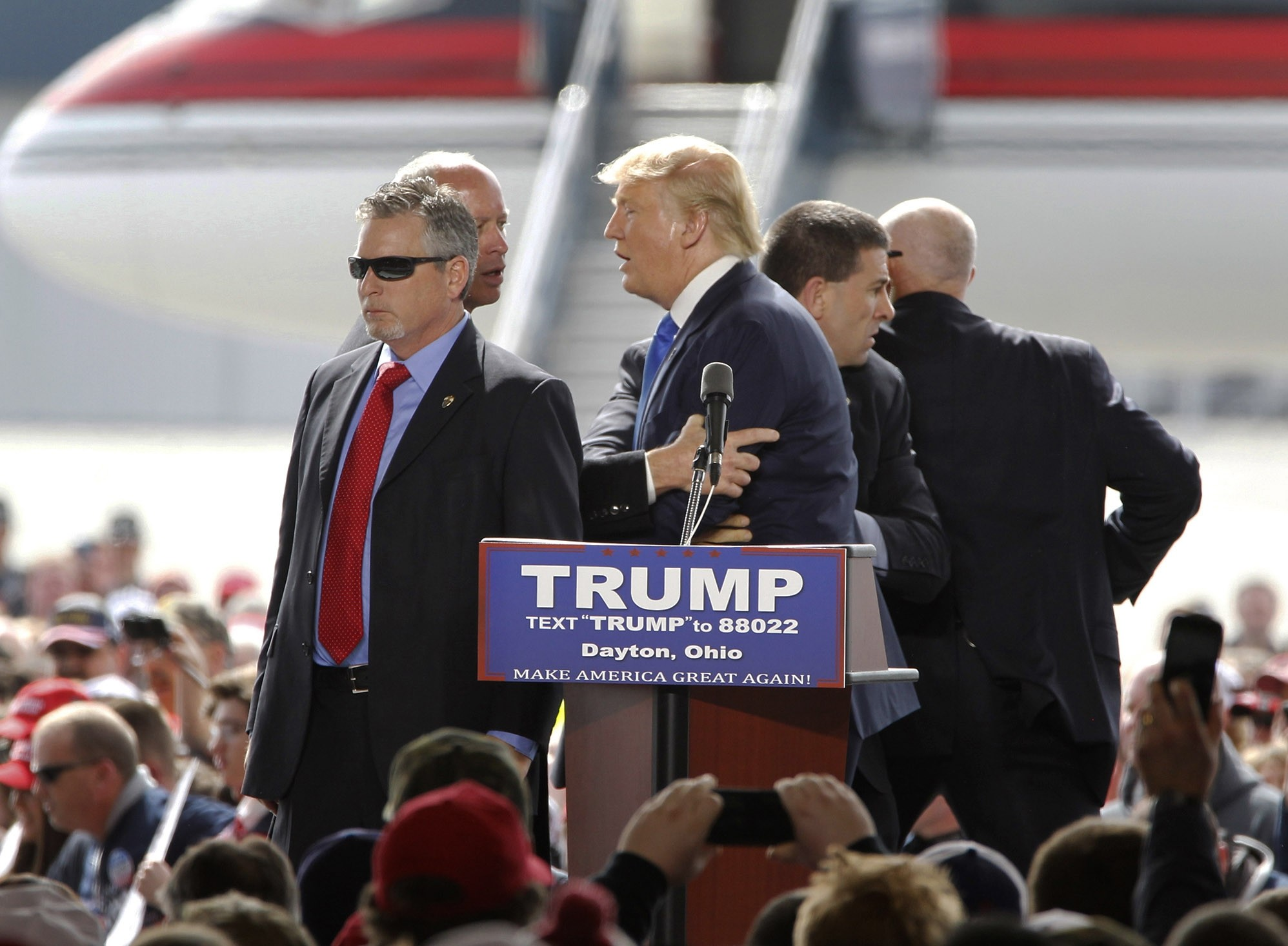 Security surround GOP presidential candidate Donald Trump after a man rushed the stage during a campaign rally at Dayton International Airport in Vandalia, Ohio. (AP Photo)