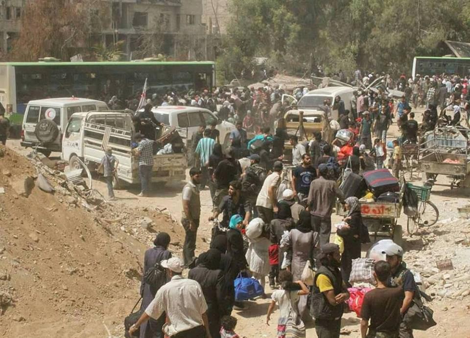People gather before being evacuated from the besieged Damascus suburb of Daraya. (Sanaa via Reuters)