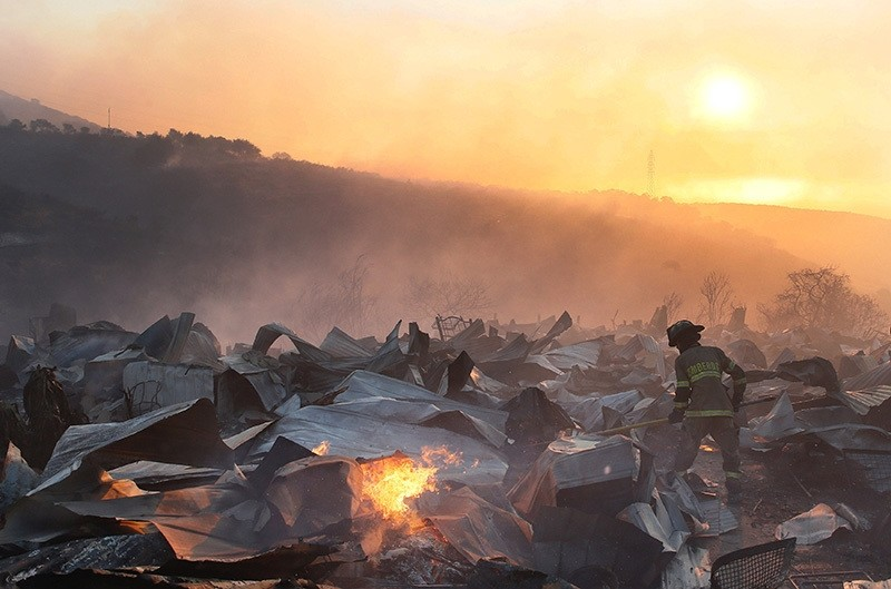 A firefighter removes the remains of a burned house on a hill, where more than 100 homes were burned due to forest fire but there have been no reports of death, local authorities said in Valparaiso, Chile, Jan. 2, 2017. (Reuters Photo)