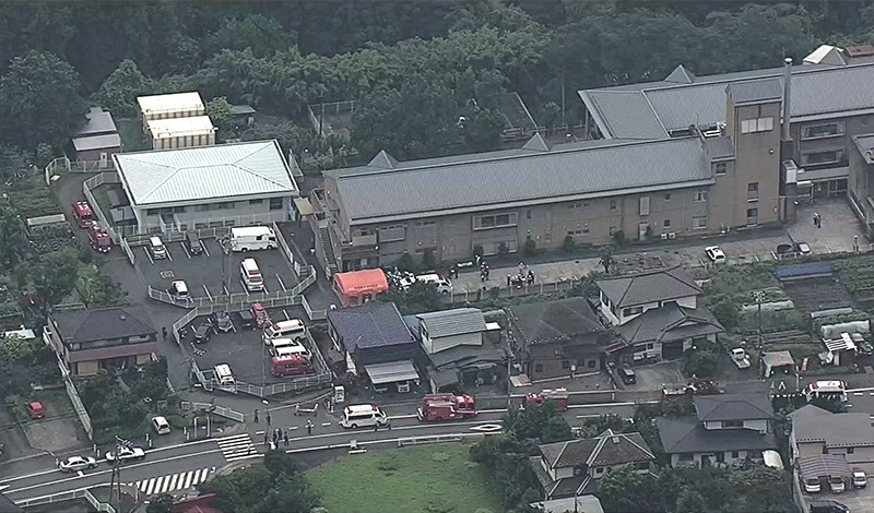 This video frame grab taken from footage supplied by Japanese broadcaster TBS on July 26, 2016 shows rescue vehicles (L) and personnel outside the Tsukui Yamayuri En care centre (AFP Photo)