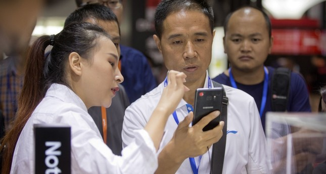 An assistant demonstrates the Galaxy Note 7 smartphone to a visitor at a Samsung Electronics display booth during an electronics expo in Beijing.