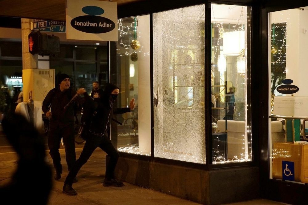 Demonstrators break a shop window during a protest against the election of Republican Donald Trump as President of the United States in Portland, Oregon, Nov. 11.