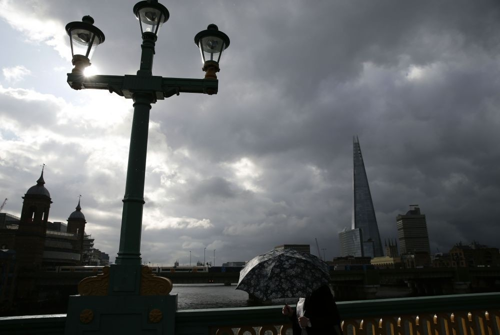 A lone commuter takes shelter from the rain beneath her umbrella as she heads to the City of London across Southwark Bridge in front of the Shard skyscraper in central London on June 27, 2016.