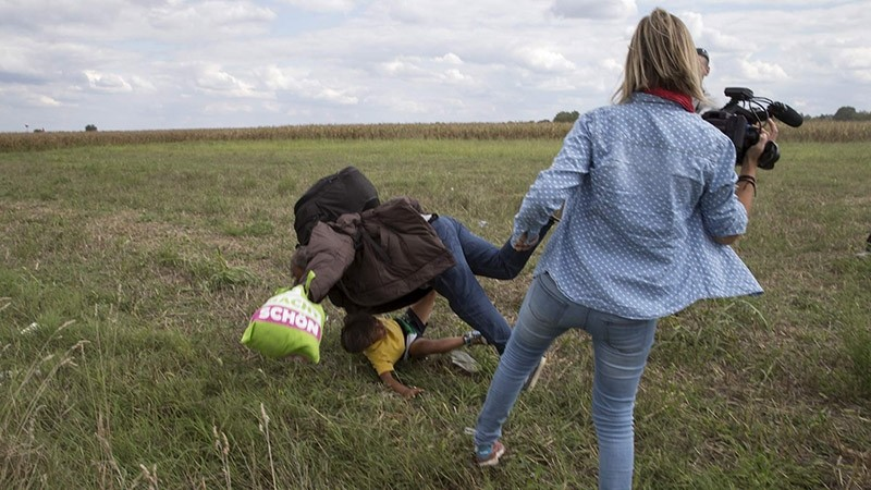A refugee carrying a child falls after tripping on TV camerawoman (R) Petra Laszlo while trying to escape from a collection point in Roszke village (Reuters Photo)