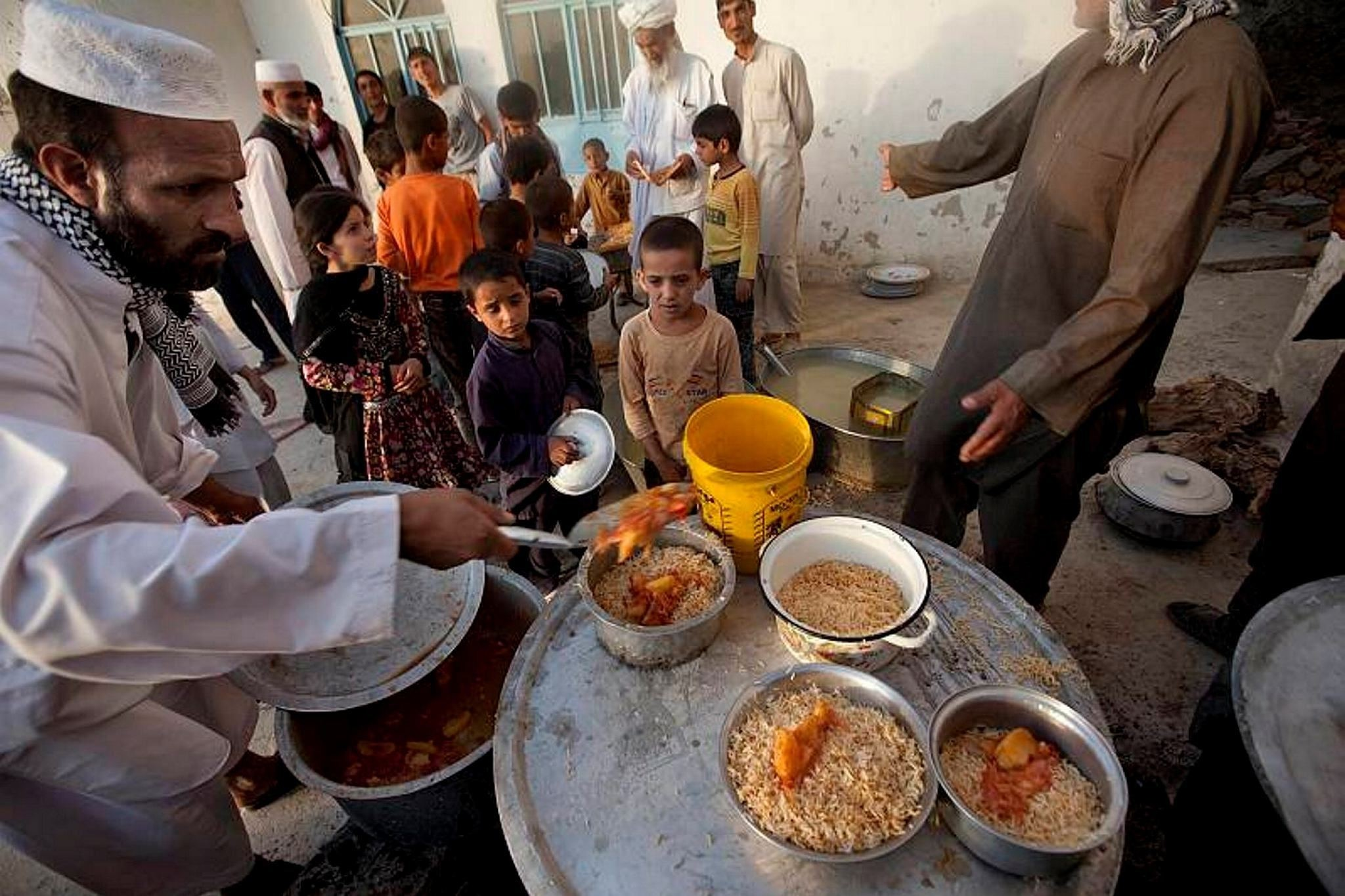 Afghan children stand in a queue as they receive food distributed on the first day of holy month of Ramadan outside a mosque in a poor neighborhood of Kabul, Afghanistan.