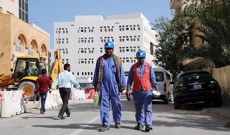 Migrant workers are seen walking next to a construction site in the Qatari capital Doha on December 6, 2016. (AFP Photo)