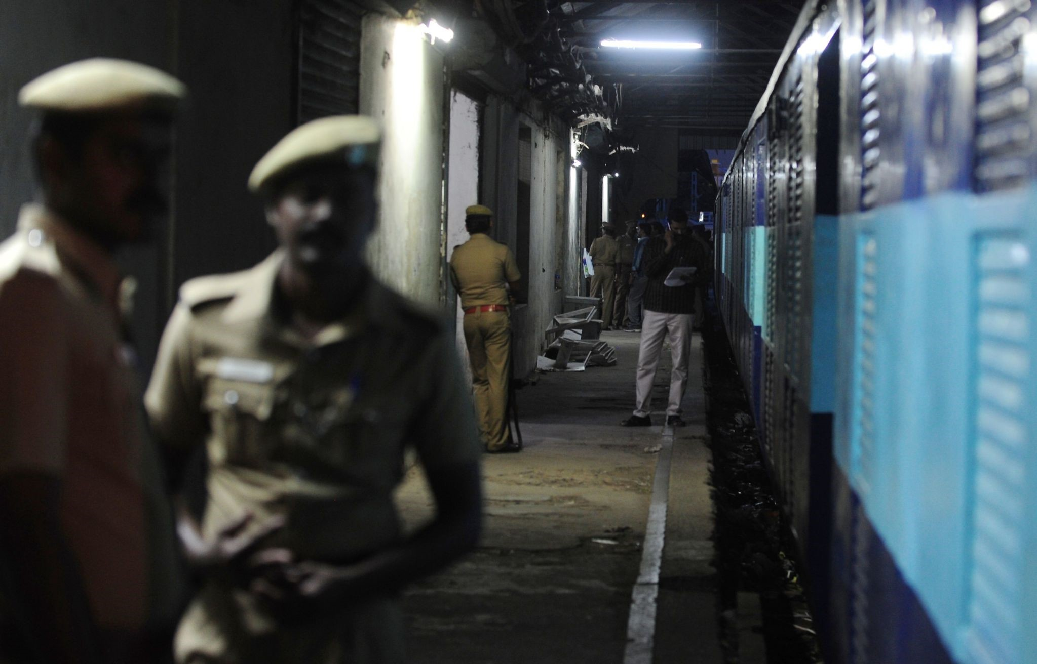 Indian police personnel stand guard alongside the Salem-Chennai Express train, which was robbed while in transit, at Egmore Railway station in Chennai on August 9, 2016. (AFP Photo)