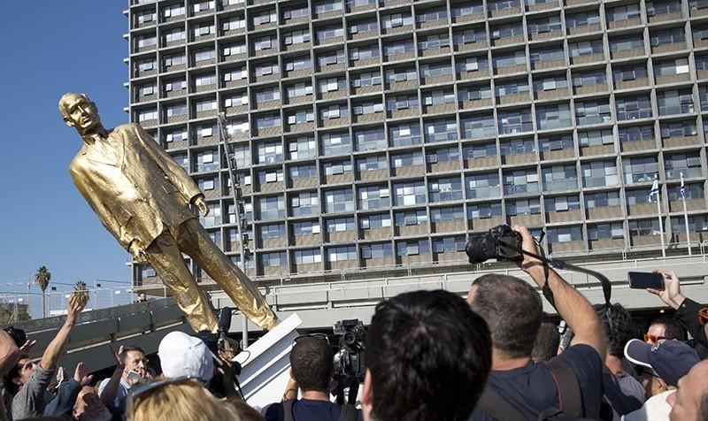 People watch a statue of Israeli Prime Minister Benjamin Netanyahu as it falls at Rabin square in Tel Aviv, Tuesday, Dec. 6, 2016 (AP Photo)