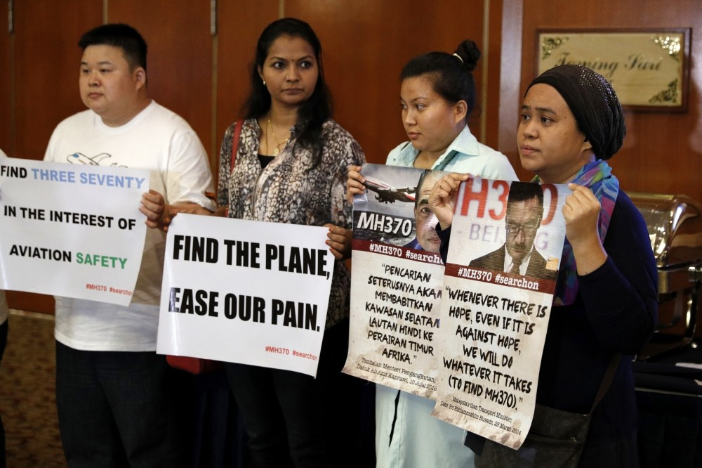 Family members of passengers on board the Malaysia Airlines Flight 370 that went missing on March 8, 2014 hold up a placards during a special press conference in Kuala Lumpur, Malaysia, July 21. (AP Photo)
