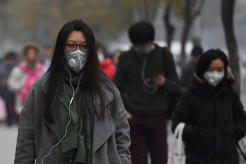 People wear masks on a polluted day in Beijing on Nov. 18, 2016. (AFP Photo)